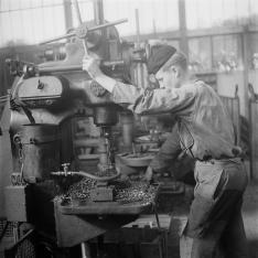 Apprenti du Service Electrique et de la Signalisation (SES) sur une machine-outil de type fraiseuse perçant une pièce métallique avec un foret au sein de Centre de formation SNCF de Moulin Neuf.